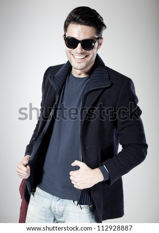 attractive man smiling and posing in the studio - stock photo