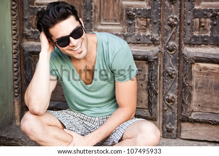 attractive man smiling wearing sunglasses - stock photo
