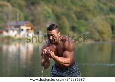 Attractive Man Standing In River And Enjoys The Nature - stock photo