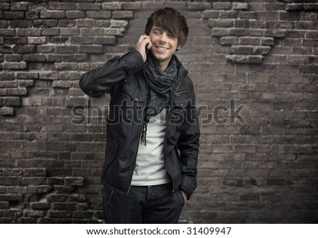 Attractive man talking over cellphone , smiling - stock photo