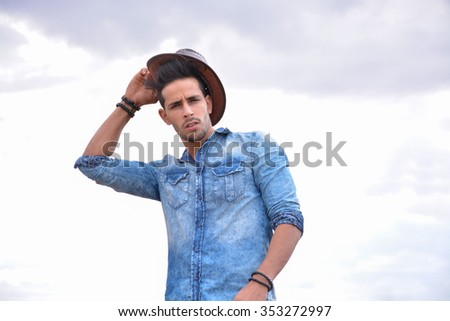 attractive man tying his hat  - stock photo