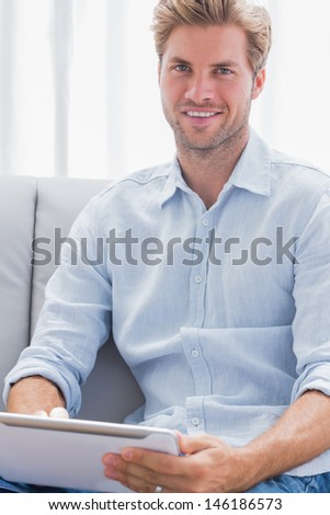 Attractive man using a tablet pc on his couch in the living room - stock photo