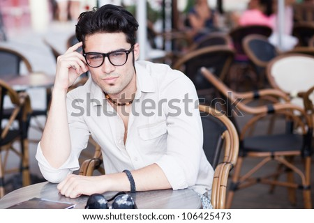attractive man wearing glasses standing at a terrace looking cool - stock photo