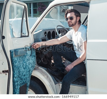 Attractive man wearing sunglasses steps out of a vintage van - stock photo