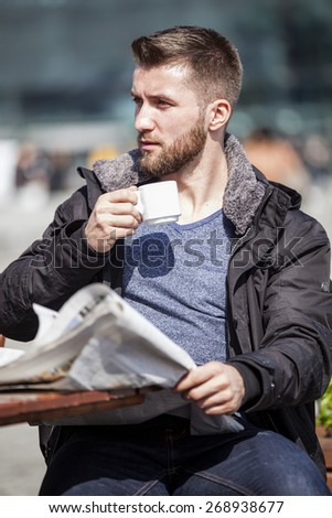 Attractive man with a beard is drinking coffee in a coffee shop - stock photo