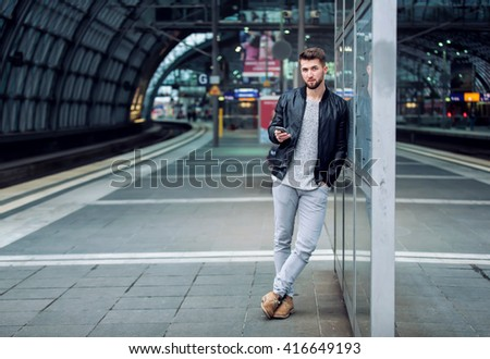 Attractive man with a beard is standing at the train station with a smart phone in his hand - stock photo