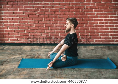 Attractive man with a beard wearing black T-shirt and blue trousers doing yoga position on blue matt at wall background, copy space, lotus asana, padmasana - stock photo