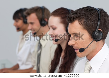 Attractive man with a headset on working in a call center with more people - stock photo