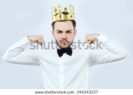 Attractive man, with beard and mustaches, wearing in white shirt, bow and gold crown, shows that he is strong, on white background, in studio, waist up - stock photo