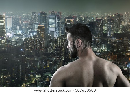 Attractive man with beard is looking from high above over the city - stock photo