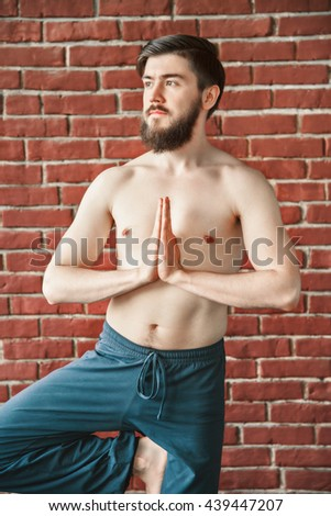 Attractive man with dark hair and beard wearing trousers doing yoga tree position on blue matt at wall background, copy space, portrait, vrikshasana asana, looking left. - stock photo
