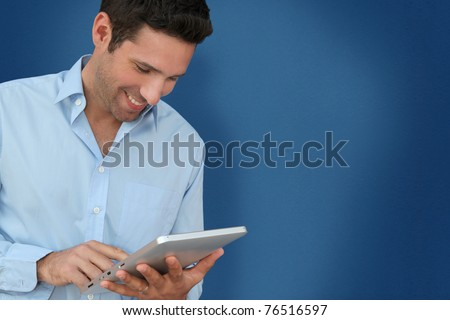 Attractive man with touchpad on blue background - stock photo