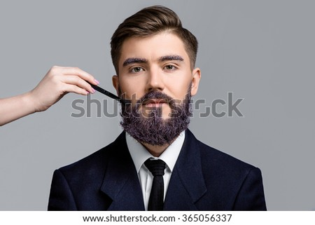 Attractive man with violet beard and eyebrows, wearing in dark blue suit and tie, looking at camera. Woman's hand with make-up brush near his face, on white background, in studio, close up - stock photo