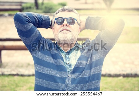 Attractive man 50 years old with beard and sanglasses - stock photo