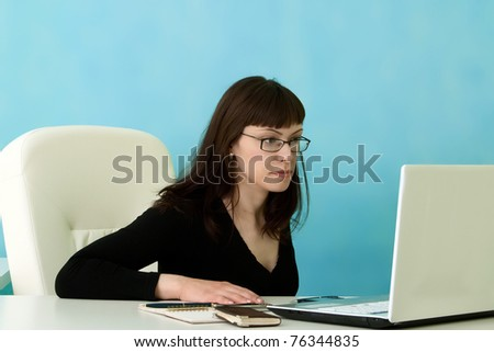 Attractive manager looking at laptop in office - stock photo