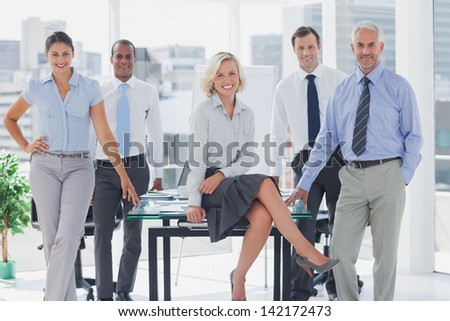 Attractive manger posing with colleagues around her in the boardroom - stock photo