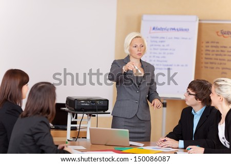 Attractive mature woman giving a business presentation to a group of diverse people seated around a table - stock photo