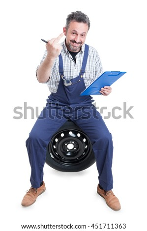 Attractive mechanic on tire showing middle finger as insulting and obscene gesture concept isolated on white background - stock photo