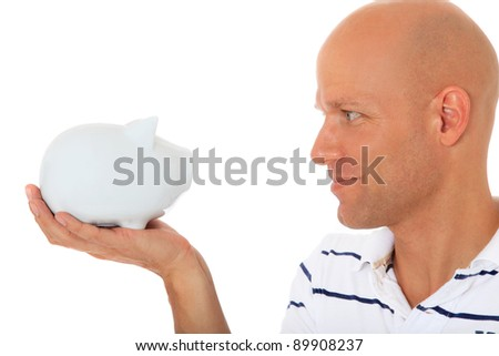 Attractive middle age man looking at piggy bank. All on white background. - stock photo