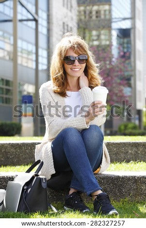 Attractive middle age woman sitting at green area while holding a cup of coffee and relaxing at coffee break. - stock photo