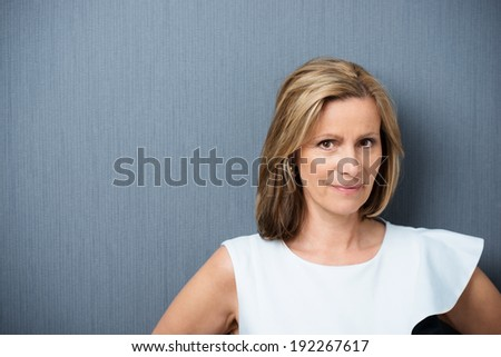 Attractive middle-aged blond woman looking at the camera with a speculative look and a feint smile of distrust against a dark grey background with copyspace - stock photo