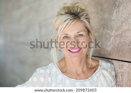 Attractive middle-aged blond woman with a beautiful smile standing against a receding wall looking directly at the camera - stock photo