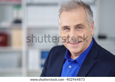 Attractive middle-aged businessman with a friendly smile looking directly at the camera, head and shoulders in the office - stock photo