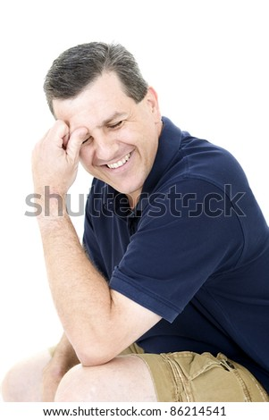 Attractive middle aged man holding his head and laughing - stock photo