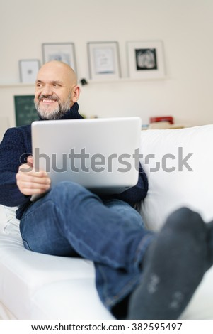 Attractive middle-aged man relaxing with a laptop computer on a comfortable sofa at home looking to the left of the frame with a happy smile - stock photo