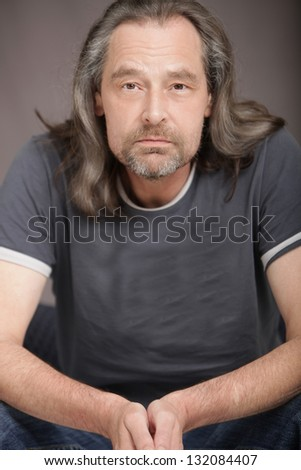 Attractive middle-aged man with a beard and long hair sitting in a chair facing the camera with a serious expression - stock photo