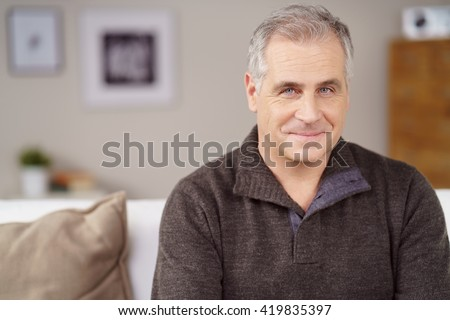 Attractive middle-aged man with a charismatic friendly smile relaxing at home on the sofa, close up head and shoulders - stock photo