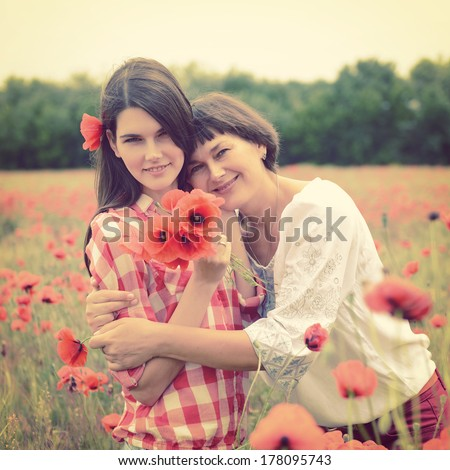 Attractive middle-aged woman have fun on a poppy field with her, summer outdoor. Image toned. - stock photo