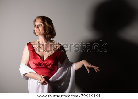 Attractive middle aged woman in a red dress with a shadow. - stock photo
