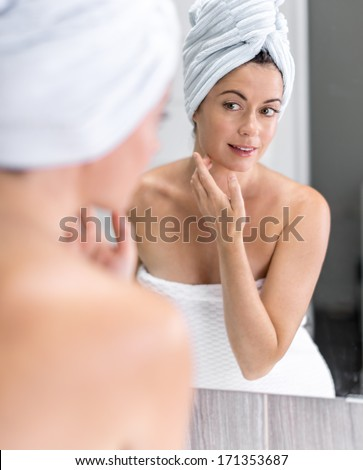 Attractive middle aged woman looking in the mirror - stock photo