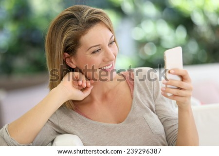 Attractive middle-aged woman messaging with smartphone - stock photo
