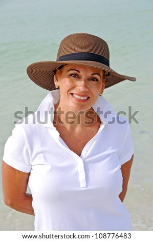 Attractive Middle Aged Woman Wearing a Sun Hat Standing on the Beach - stock photo