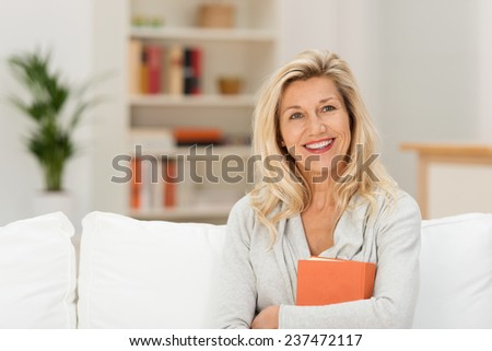 Attractive middle-aged woman with a lovely smile sitting on a sofa in the living room clutching a book - stock photo