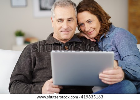 Attractive middle ahead male and female couple sitting close together on sofa while looking at open laptop computer with pleasant expression - stock photo