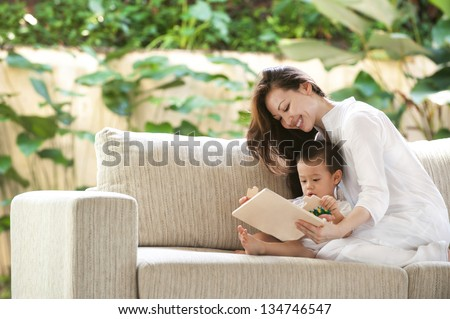 Attractive mixed female lifestyle playing puzzle with child - stock photo