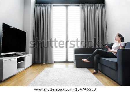 Attractive mixed female lifestyle watching tv at home - stock photo