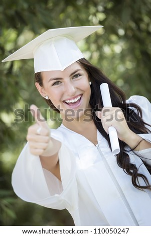 Attractive Mixed Race Girl Celebrating Graduation Outside In Cap and Gown with Diploma in Hand. - stock photo
