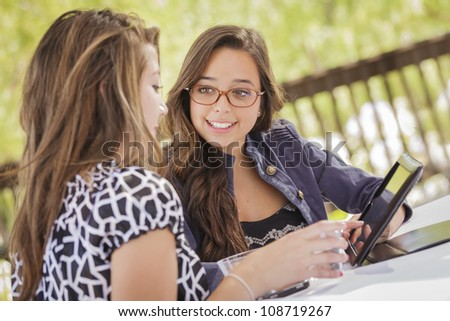 Attractive Mixed Race Girls Smiling and Talking While Working on Tablet Computer Sitting Outdoors. - stock photo