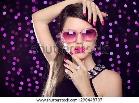 Attractive Model with sunglasses. Beauty girl portrait with pink lips makeup, manicured polish nails and luxury gemstone necklace over party lights background. - stock photo
