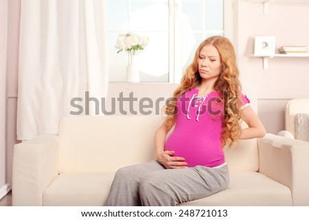 Attractive 7 months pregnant woman massaging her back sitting on the sofa - stock photo