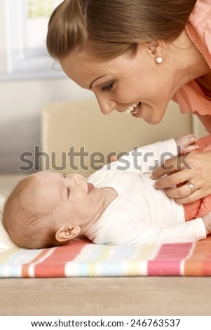 Attractive mother and baby laughing, having fun. - stock photo