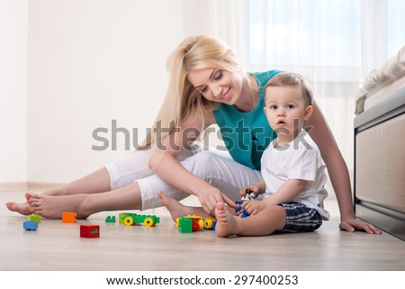 Attractive mother plays with her child on the floor. She is smiling and looking at toys. Her son is looking at the camera seriously - stock photo
