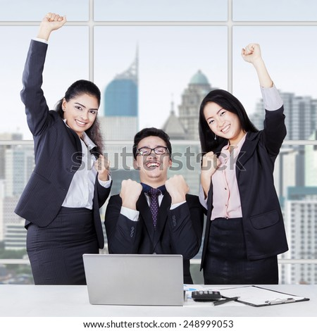 Attractive multi ethnic business team celebrating their success at the workplace - stock photo