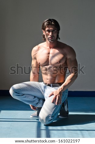 Attractive muscleman kneeling shirtless on grey background wearing jeans - stock photo
