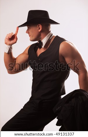 Attractive muscular male model wearing waistcoat and black hat - stock photo