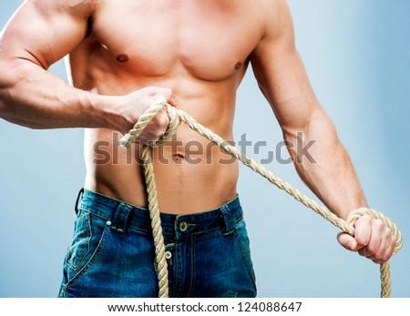 Attractive muscular man torso rope breaks - stock photo